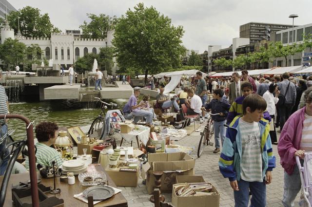 TLB023000337_001 - Bezoekers op de jaarlijkse Meimarkt. Een 24-uurs rommelmarkt die een groot deel van de Tilburgse binnenstad beslaat. Op de achtergrond links staat het oude Paleis Raadhuis en rechts appartementencomplex de Frankenhof en het Gerechtsgebouw