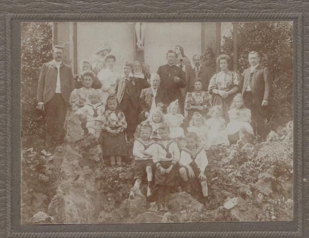 045133 - De familie Eras op bezoek bij de ursulinen in Hamont. Zittend in het midden Jan Baptist Eras, fabrikant en regent van het r.k. gasthuis, geboren te Tilburg op 26 september 1831 en aldaar overleden als weduwnaar van Anna Maria Mercx op 13 december 1906. Links achter hem zijn dochter Anna Maria Jacoba Eras, ursulin te Hamont met de kloosternaam Herman Jozef van de H. Geest. Zij werd geboren te Tilburg op 11 juli 1868 en overleed te Hamont op 13 oktober 1942. Rechts achter Jan Baptist zijn zoon mgr.dr. Bernardus Josephus Eras, priester, procurator van het Nederlands episcopaat te Rome, rector van het Nederlands priestercollege aldaar, ere-kanunnik van de kathedraal van St. Jan te 's-Bosch en ere-kapelaan van de Souvereine Orde van Malta. Hij werd geboren te Tilburg op 21 augustus 1876 en overleed te Arnhem op 11 augustus 1952. Geheel links bovenaan schoonzoon Lambertus Thomas Maria de Beer, textielfabrikant, geboren te Tilburg op 7 juli 1867 en aldaar overleden op 31 mei 1931. Rechts voor hem ziitend, zijn vrouw Theresia Catharina Huberdina Maria Eras, geboren te Tilburg op 19 april 1870 en aldaar overleden op 18 juni 1957. Zittend rechts van Jan Baptist Eras zijn dochter Maria Cornelia Jacoba Eras, geboren te Tilburg op 21 november 1865 en aldaar overleden op 16 december 1932. Staande achter haar, haar man Carolus Sebastianus Janssens, textielfabrikant, geboren te Tilburg op 23 februari 1857 en aldaar overleden op 19 juni 1939. Staande rechts van hem Johanna Maria Dionysius Blomjous geboren te Tilburg op 13 augustus 1870 en aldaar overleden op 28 oktober 1947. Zij was presidente van de St. Elisabethvereniging. Staande geheel rechts haar man Petrus Hermanus Maria Eras, ook een zoon van Jan Baptist. Hij werd geboren te Tilburg op 1 januari 1867 en overleed te 's-Hertogenbosch op 16 juni 1932. In Tilburg was hij textielfabrikant, voorzitter van de r.k. stichting kerkenbouw, lid van het kerkbestuur en de St. Vincentiusvereniging van de parochie Heike en regent va