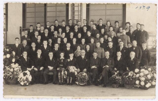 039088 - Volt. Jubileum. Het 25-jarig dienstjubileum van de heer Hubert van de administratie in 1939 bij Volt. Hubert was de eerste (1917) benoemde procuratiehouder van Volt. Dit was ook het eerste zilveren jubileum dat bij Volt werd gevierd. Men kan dit zien als een teken des tijds. Immers Fien van Geloven, de eerste medewerkster van Volt en vanaf de oprichting in 1909 in dienst van het bedrijf, viel deze eer in 1934 niet ten deel. Wél kreeg ze toen een hortensia die tijdens haar 40 jarig jubileum nog in leven was.Later, in 1949 bij het 40-jarig bestaan van Volt, werd dit goed gemaakt en vierde Fien ook haar 40-jarig jubileum. Voltstraat heette toen Nieuwe Goirlese weg