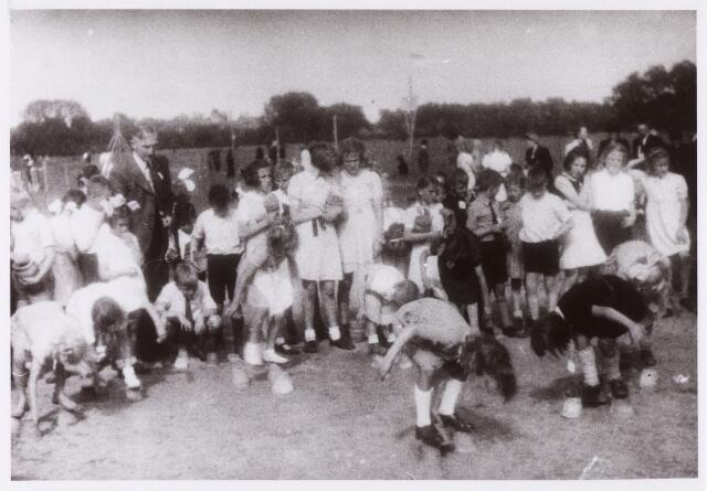 013637 - Tweede Wereldoorlog. Drukte op een terrein aan de Ringbaan-Zuid, waar op 16 juli 1944 kinderspelen werden georganiseerd ten behoeve van de vrijwillige luchtbescherming. Hier lopen de kinderen op conservenblikjes