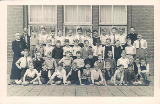 651841 - Tilburg. Een groepsfoto van leerlingen van een rooms katholieke (zie begeleidende frater) lagere jongensschool (basisschool).