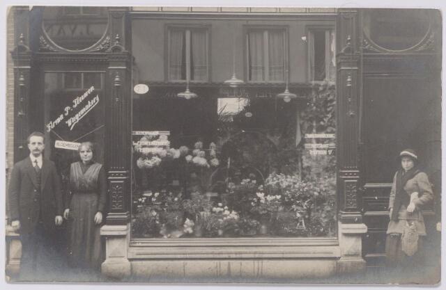 043981 - Winkelbedrijf. De bloemenzaak van de firma Teeuwen en Wagemakers aan de Heuvelstraat 71. Tuinman Jacobus Teeuwen, geboren te Ginneken op 16 juni 1830 vestigde zich in Tilburg met zijn vrouw Adriana Johanna van der Kar, geboren te Antwerpen op 5 september 1843. Na het overlijden van Jacobus te Tilburg op 3 oktober 1888 hertrouwde zij met bloemist Peter Johannes Teeuwen, geboren te Budel op 25 juli 1857. Alleen uit het eerste huwelijk werden kinderen geboren. Adriana Johanna van der Kar overleed te Tilburg op 4 oktober 1915. Na haar dood werd de zaak gesplitst.In het ouderlijk huis aan de Piusstraat ging zoon Alphonsus F.C. Wagemakers wonen met zijn vrouw, Petronella J.Th. Favier uit Hilvarenbeek, en zijn stiefvader. Alphons was bloemist van beroep. Drie ongetrouwde kinderen van Adriana Johanna van der Kar gingen wonen in het pand Heuvelstraat 71 en begonnen daar een bloemenwinkel. Op de foto staat geheel links Constantinus Joannes (Stan) Wagemakers, bloemist van beroep, geboren te Tilburg op 29 augustus 1884 en aldaar ongehuwd overleden op 20 december 1929. Rechts van hem zijn zus Maria Catharina Adriana Wagemakers, geboren te Tilburg op 22 juli 1877, winkelierster van beroep. Zij vertrok in 1927 ambtshalve naar Parijs en trouwde later met  Henricus Augustinus van Gastel. Zij overleed te Tilburg op 27 april 1967. Verder woonde in dit pand hun broer Leonardus Jacobus Wagemakers, geboren te Tilburg op 18 april 1883 en aldaar ongehuwd overleden op 4 februari 1950. Hij was autohandelaar van beroep. Stiefvader Teeuwen overleed te Tilburg in 1935. Hij was penningmeester van de St. Ambrosiusvereniging en in 1919 medeoprichter van de Groente Veiling in Tilburg. In 1949 vierde bloemisterij Teeuwen-Wagemakers haar 100-jarig bestaan