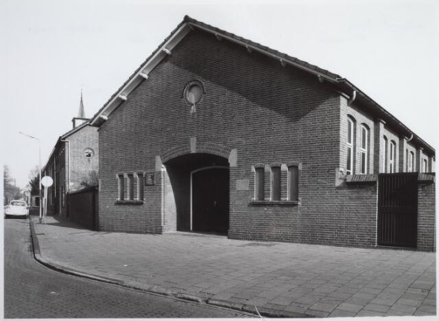 026444 - Hervormde kerk aan de Minister Mutsaersstraat. Boven de huizen de torenspits van de Theresiakerk