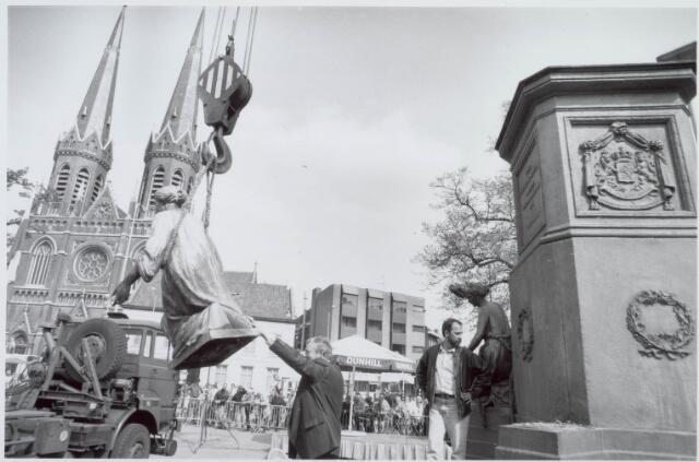 021478 - Een van de vier vrouwenfiguren rond het standbeeld van Willem II hangt in de takel. In 1993 werd het beeld tijdelijk verwijderd ten behoeve van een grondige schoonmaakbeurt. Militairen zorgden voor het transport en de kosten van deze operatie