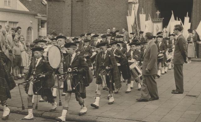 653324 - Parochie Gasthuisring. Tijdens de processie voor de overbrenging van het Allerheiligste van de oude kerk naar de nieuwe, loopt de drumband 'De Schotjes' ook mee.