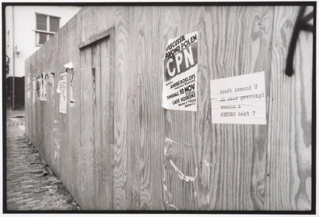 033585 - Aanplakbiljetten op de schutting ter afscherming van een afgebroken pand aan de Tuinstraat met daarop het rode fietspad