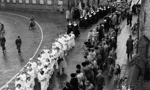 063776 - Bruidjes en zusters verlaten de parochiekerk, waar een plechtige hoogmis werd opgedragen door pastoor Van Riel ter gelegenheid van de viering van het 75-jarig bestaan van het succursaalhuis van de zusters in Goirle.