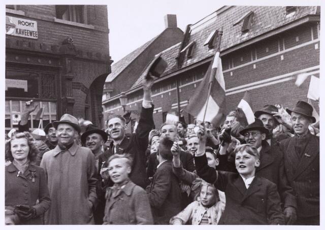 013336 - WO2 ; WOII ; Tweede Wereldoorlog. Bevrijding. Getooid met Nederlandse vlaggen begeven opgeluchte Tilburgers zich naar de Markt. Uiterst links Jeanne Vermeer, destijds woonachtig in de Van Sonstraat, evenals de toen 16-jarige Harrie van Gils, derde van links. De man met hoed rechts is Johan Lammers en de met een vlag zwaaiende man naast hem is Wolter ter Riele, beiden wonende in de Jan Trompstraat