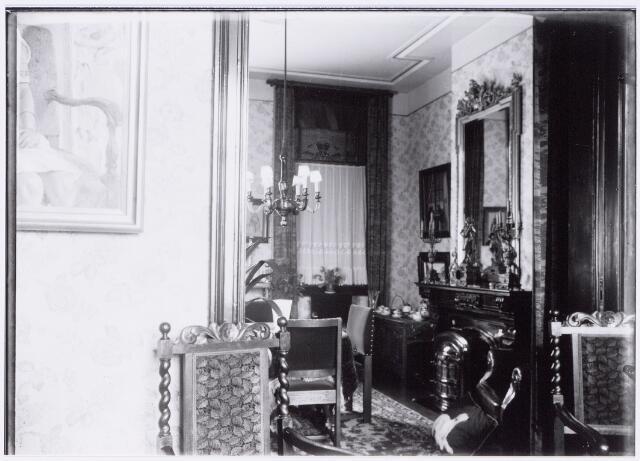 049858 - Foto uit ´Je Taalboek´ van frater Victor van Nispen. Kijkje in de voorkamer van een Tilburgs herenhuis. Op de schouwmantel een klokkenstel. In de hoek, naast de kolenkachel, een theekastje.