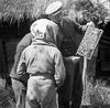 De heer Abraham Hage toont een jongen een honingraat.