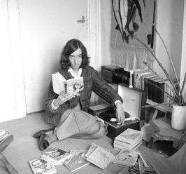 Diet Verschoor op haar kamer met boeken en grammofoon; lezen