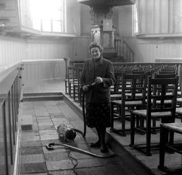kosteres J. Reinhoudt maakt de kerk schoon; stofzuiger