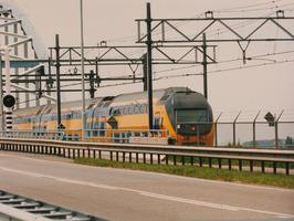 Passerende trein op het spoor. Ernaast ligt de N289 (Goes-Putte) bij de Vlakebru…