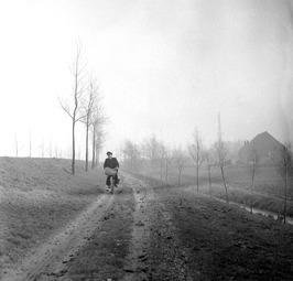 postbode fietsend richting Arnemuiden over onverharde weg