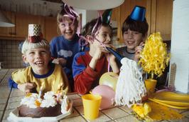 kinderen met toeters, hoedjes en taart