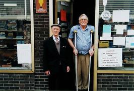 Aaldrik de Vries in de deuropening van zijn winkel aan de Kanaalweg 110; links b…