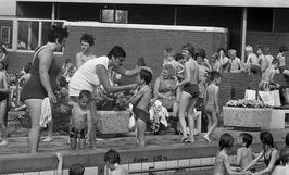 een jongetje krijgt een standje op een drukke dag in het zwembad