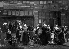 Visverkoop door vrouwen in Walcherse klederdracht, manden, handkar.