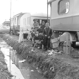 kinderen spelen tussen woonwagens; Wegens de kanaalverbredingswerken werd het wo…
