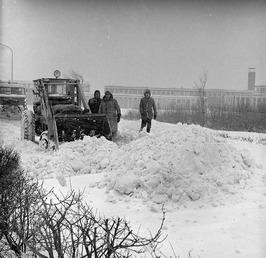 een bulldozer ruimt sneeuw en effent het pad voor een op de Koudekerkseweg tusse…