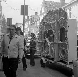 Mevrouw Gouweloos bij straatorgel De Staer, met centenbakje.