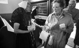 Twee vrouwen in klederdracht in een kerk tijdens de openstelling van kerken van …
