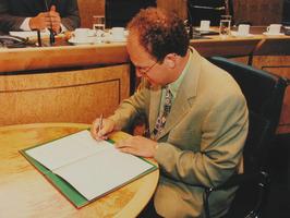 Gedeputeerde G. de Kok tekent een akkoord met de Zeeuwse Bibliotheek .