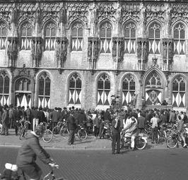 artiesten van circus Boltini tonen hun kunsten voor het stadhuis; fietsen, bromm…