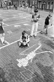 Op straat tekenen met stoepkrijt op Koninginnedag.