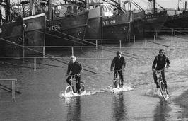 extreme hoogwaterstand; wateroverlast; kinderen op fiets in water; hoog water
