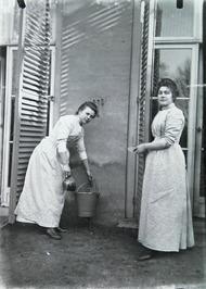 dienstmeisjes Cato Abrahamse (rechts) en Marina van de familie Bolle; emmer met …